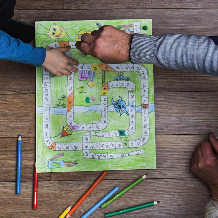 Adult playing a board game with a child